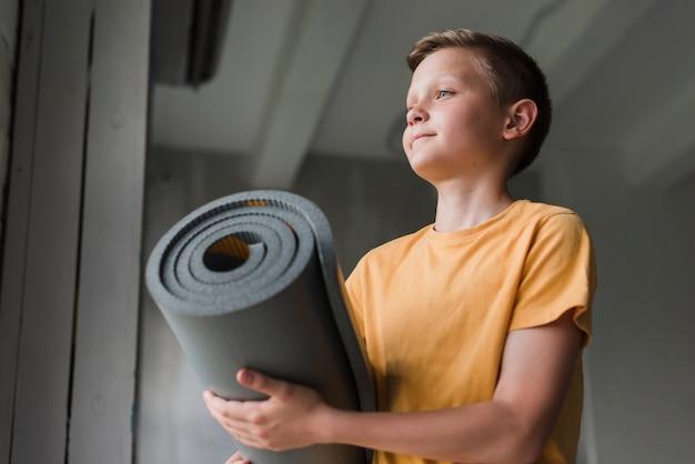 Opinión de ángulo bajo del muchacho que sostiene la estera gris rodante del ejercicio