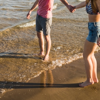 Opinión de ángulo bajo de los pares jovenes que se sostienen la mano de cada uno que se coloca cerca de la costa de mar