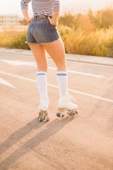 Opinión de ángulo bajo de la pierna de la mujer que lleva los pcteres de ruedas del vintage que se colocan en el camino