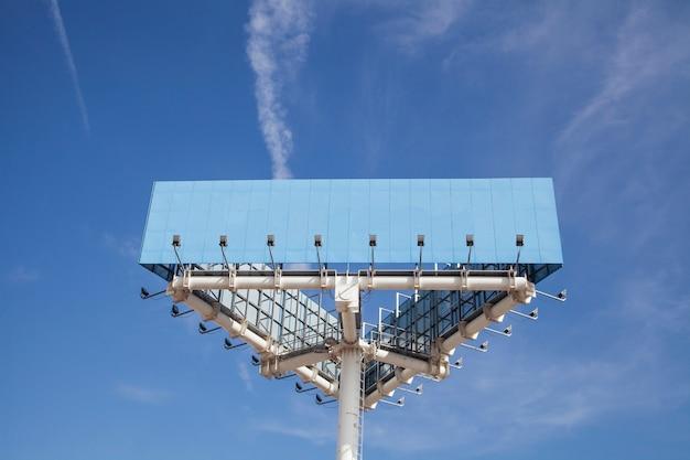 Opinión de ángulo bajo del polo de acaparamiento grande azul con la luz contra el cielo azul