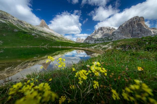 Opinión asombrosa de los paisajes del estanque y de la montaña verde con el cielo azul el verano de las dolomías, italia.