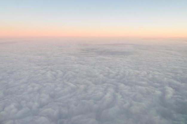 Opinión del iluminador del aeroplano sobre las nubes mullidas y el cielo de la salida del sol. vista de las nubes desde el iluminador del avión