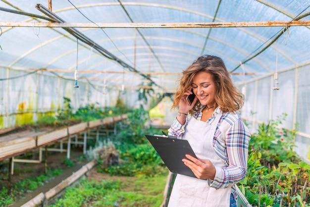 Opinión una mujer atractiva joven que trabaja en el cuarto de niños de las plantas usando smartphone