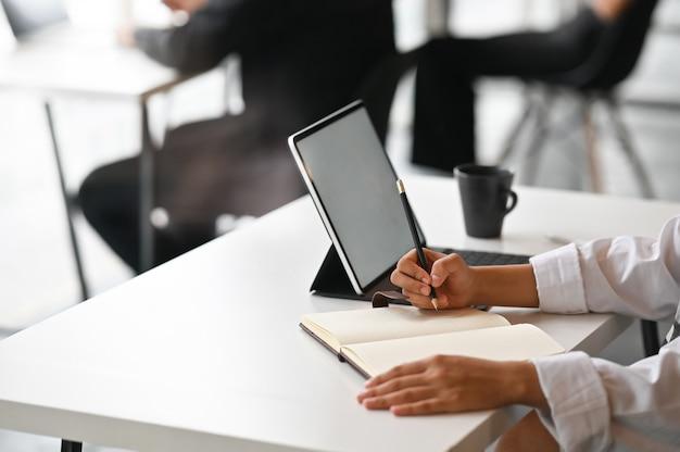 Opinión del primer la empresaria joven que trabaja en su plan que escribe la idea en el cuaderno con la tableta digital.