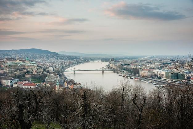 Opinión de la puesta del sol de la ciudad de budapest en un día nublado.