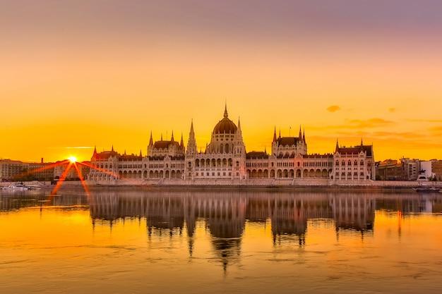 Opinión de la puesta del sol del edificio del parlamento de budapest con el río danubio en hungría.