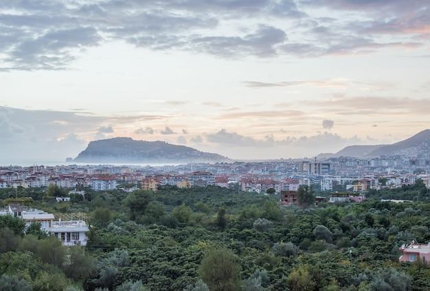 Opinión de la puesta del sol del puerto, del mar y de la fortaleza en alanya, turquía.