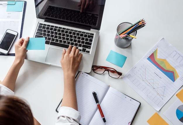 Opinión superior la empresaria que sostiene la nota y que trabaja con el ordenador portátil mientras que se sienta en el escritorio de oficina