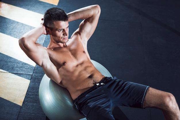 Opinión superior el hombre joven que ejercita en bola del ejercicio