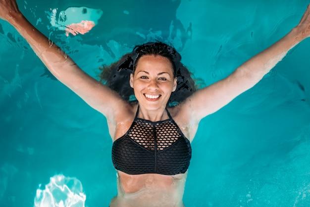 Opinión superior la mujer joven atractiva con sonrisa auténtica en la piscina.