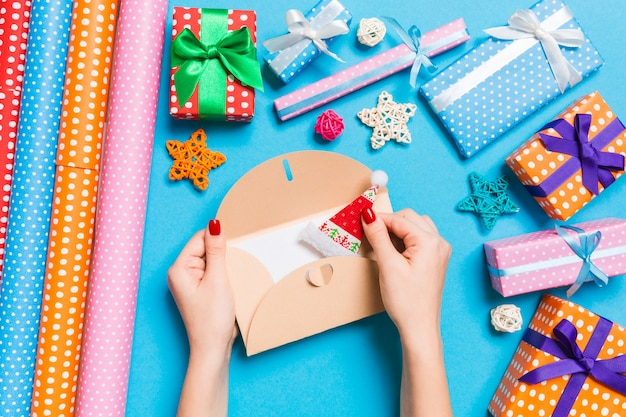 Opinión superior la mujer que sostiene un sobre, decoraciones del día de fiesta. concepto de tiempo de navidad