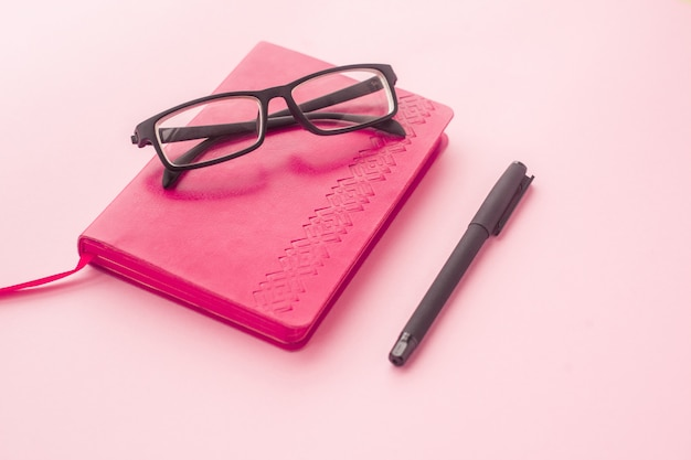 Opinión superior rosada del diario, de la pluma y de los vidrios sobre un fondo rosado. enfoque selectivo