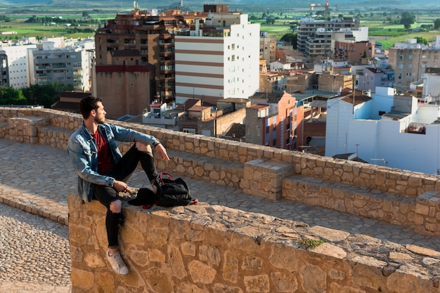 Opinión trasera el hombre joven que mira la ciudad del tejado del castillo. concepto de estilo de vida y libertad.