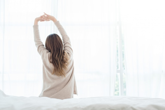 Opinión trasera la mujer asiática joven hermosa feliz que despierta por la mañana, sentándose en cama