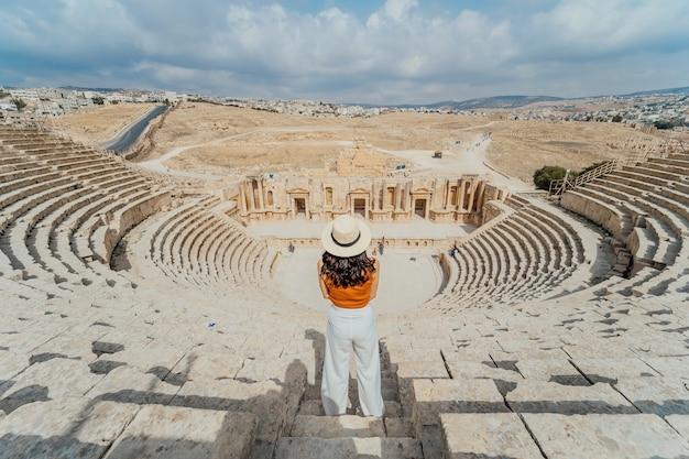 Opinión trasera la mujer joven asiática que se coloca delante del teatro romano del sur, jerash, jordania
