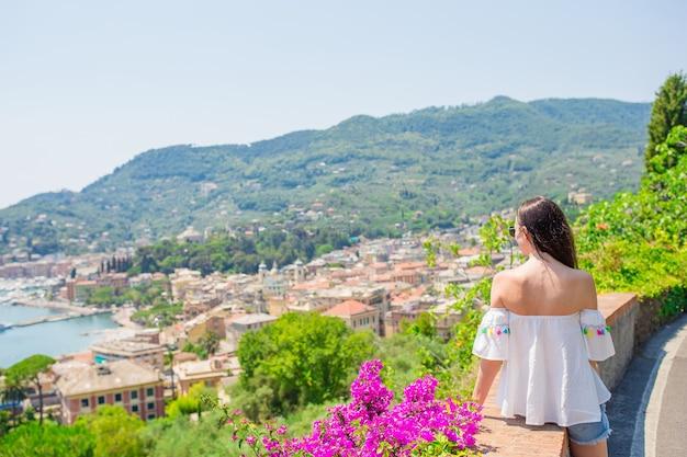Opinión trasera la mujer joven en una ciudad imponente. turista que mira la vista escénica de rapallo, cinque terre, liguria, italia