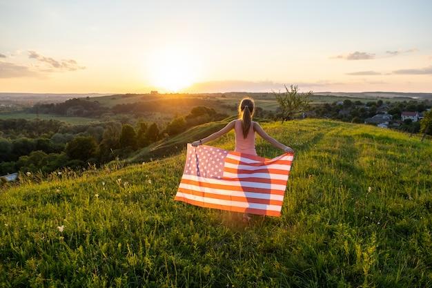 Opinión trasera la mujer joven feliz que presenta con la bandera nacional de los eeuu que se coloca al aire libre al atardecer. chica positiva celebrando el día de la independencia de estados unidos. concepto del día internacional de la democracia.