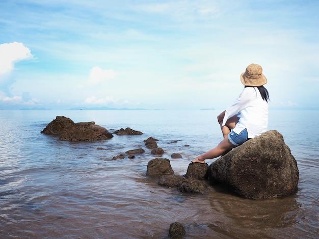 Opinión trasera la mujer joven feliz que se sienta en la roca y que mira al océano.
