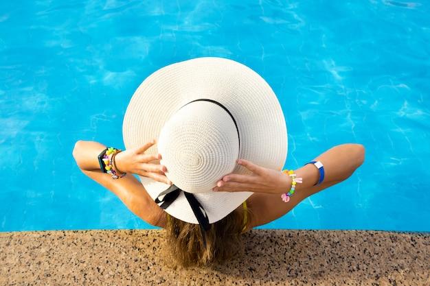 Opinión trasera la mujer joven con el pelo largo que lleva el sombrero de paja amarillo que se relaja en piscina caliente del verano con agua azul en un día soleado.