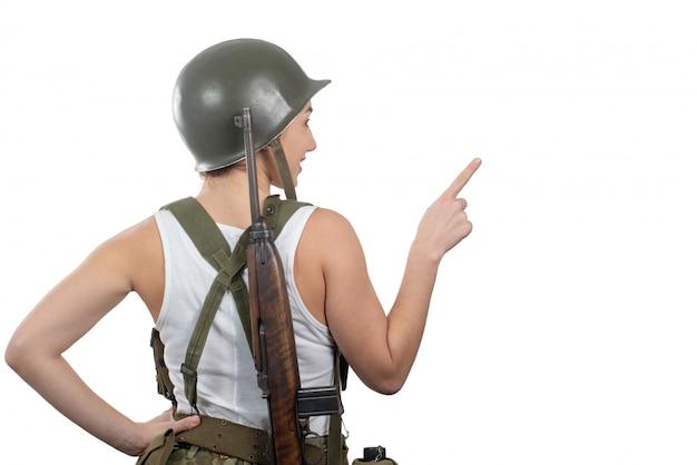 La opinión trasera la mujer joven se vistió en el uniforme militar americano ww2 que mostraba el letrero en blanco vacío