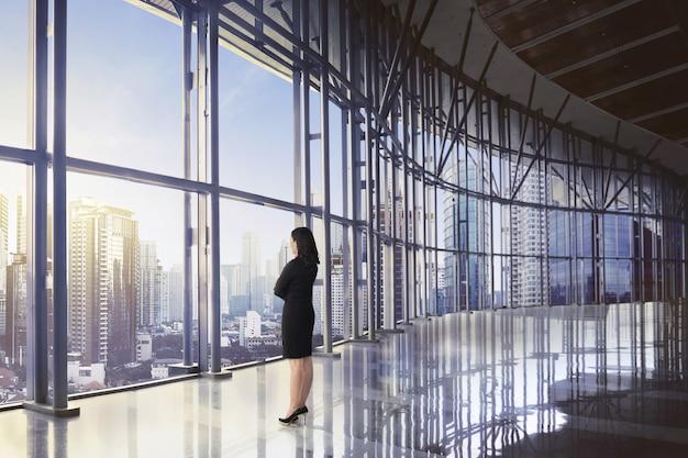 Opinión trasera la mujer de negocios asiática que se relaja mientras que mira el rascacielos