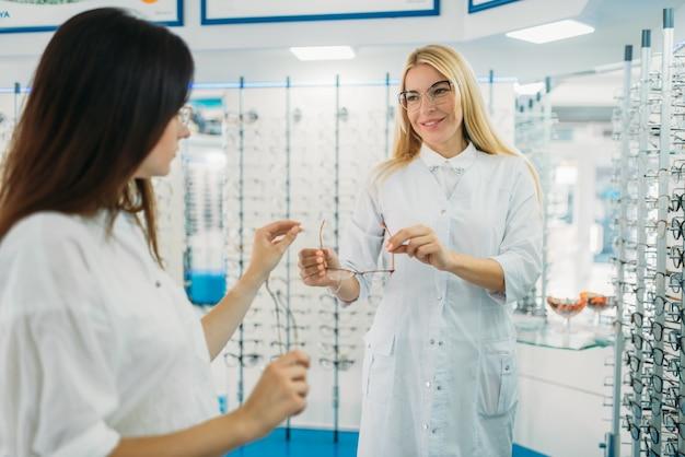 Óptica femenina muestra anteojos al comprador en la tienda de óptica. selección de anteojos con optometrista profesional.