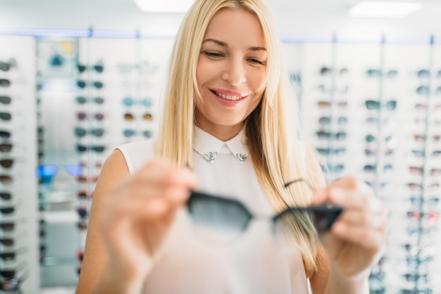 Óptica femenina muestra gafas de sol en la tienda de óptica. selección de protección ocular con optometrista profesional, concepto de optometría