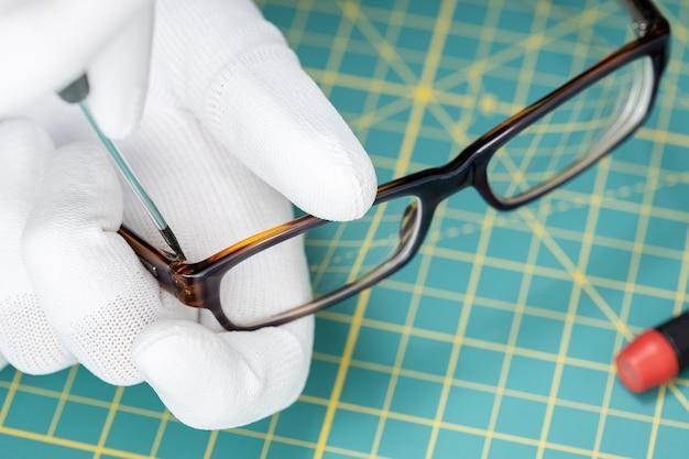 Óptico manos en guantes reparación de anteojos con una herramienta.