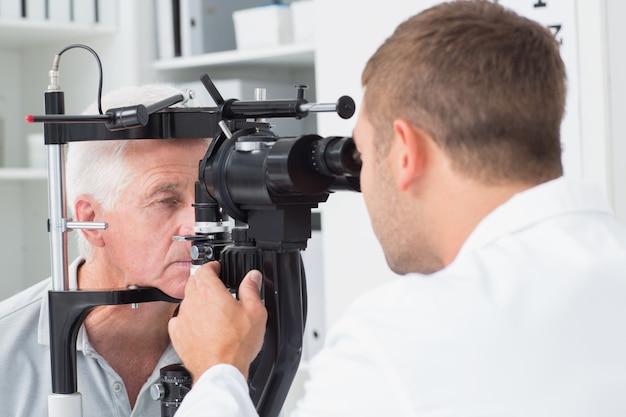 Óptico que examina los ojos de pacientes mayores a través de la lámpara de hendidura
