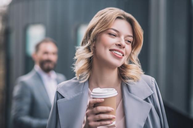 Optimismo. feliz joven mujer de negocios con cabello rubio ondulado tomando café en la tarde al aire libre y el hombre a distancia