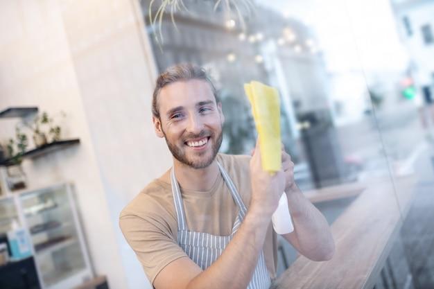 Optimista. feliz joven adulto en camiseta y delantal de rayas limpiando el vidrio mientras está en el café