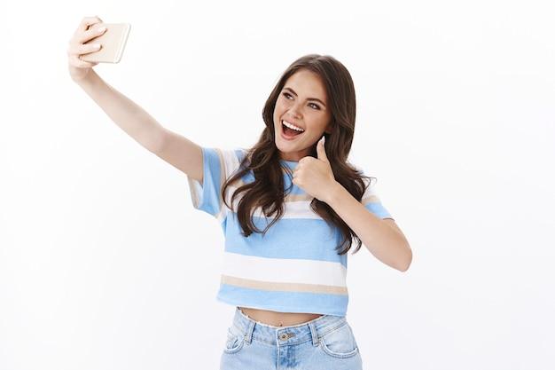 Optimista mujer linda afortunada que se siente feliz, viaja por el mundo tomando selfies, extiende el brazo con el teléfono inteligente sonriendo alegremente, posa cerca de un hermoso espectáculo turístico con el pulgar hacia arriba gesto de aprobación
