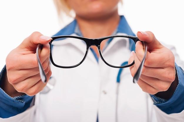 Optometrista femenina dando gafas nuevas