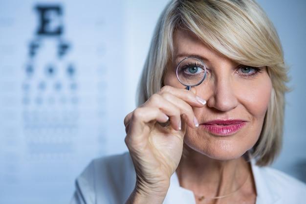 Optometrista femenina mirando a través de la lupa