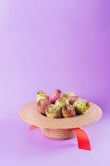 Opuntia fruta en un sombrero de paja sobre un fondo morado de moda