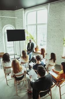 Orador afroamericano masculino dando presentación en la sala en el taller audiencia o sala