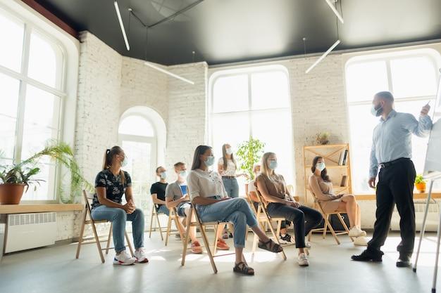 Orador masculino dando presentación en la sala en el taller de la universidad audiencia o sala de conferencias