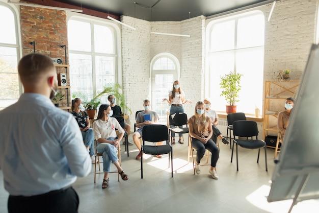 Orador masculino dando presentación en la sala en el taller universitario audiencia o conferencia