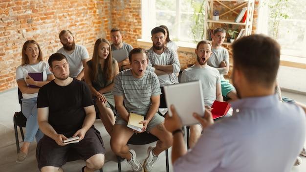 Orador masculino dando presentación en taller universitario. audiencia o sala de conferencias. uso de tableta y rotafolio para visualización de información. evento de conferencia científica, formación. educación.