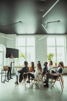 Oradora afroamericana dando presentación en el salón del taller. audiencia o salón. vista lateral de los participantes en la audiencia. evento de conferencia, formación. educación, diversidad, concepto inclusivo.