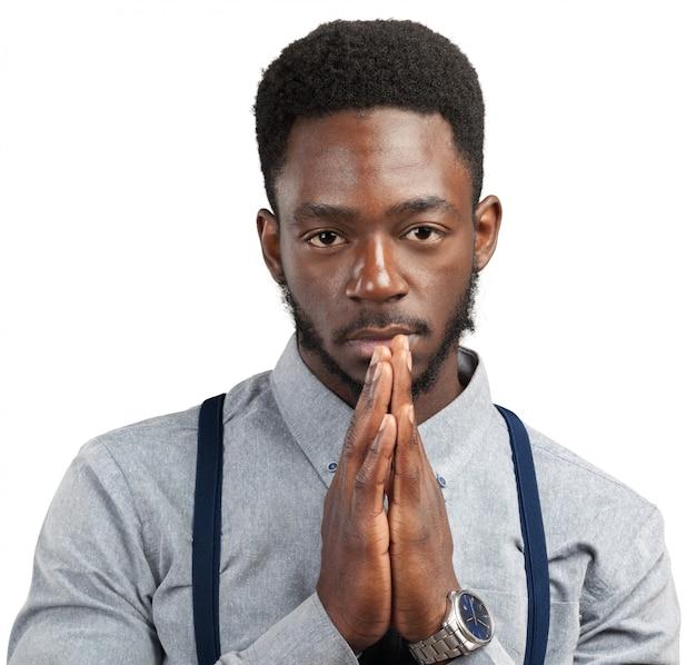 Orando a un joven afroamericano presionando las manos juntas