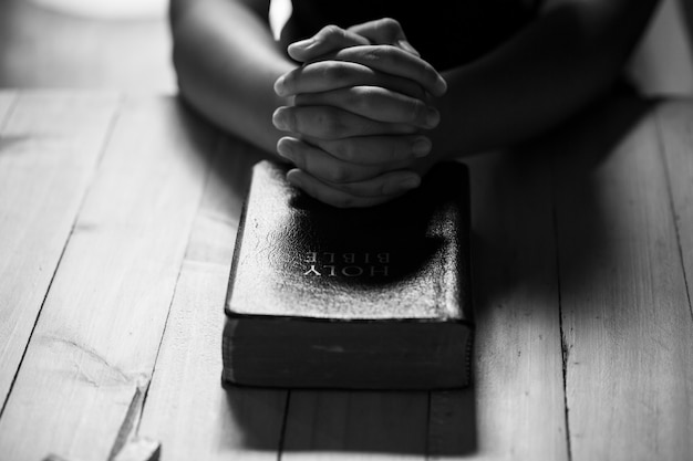Orando las manos de los adolescentes en la vieja biblia