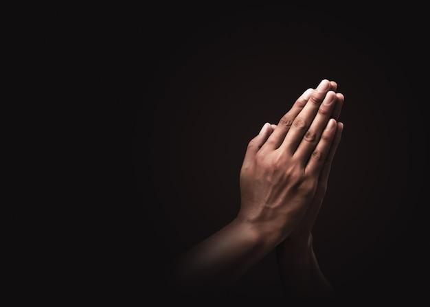 Orando manos con fe en la religión y creencia en dios en la oscuridad. poder de esperanza o amor y devoción. namaste o namaskar manos gesto. posición de oración.