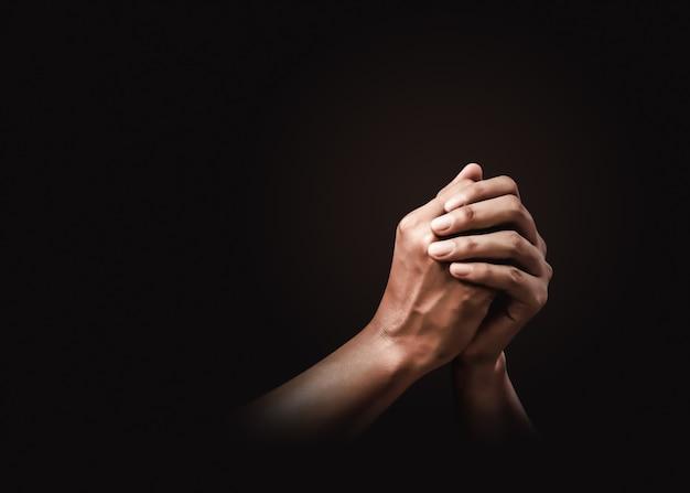 Orando manos con fe en la religión y creencia en dios en la oscuridad. poder de esperanza o amor y devoción.