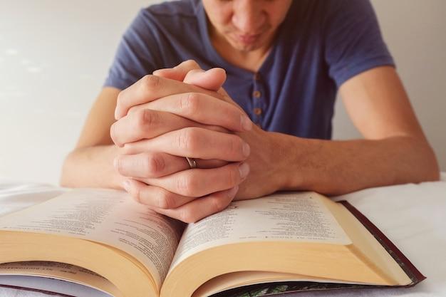 Orando las manos de un hombre sobre la biblia abierta en la cama blanca