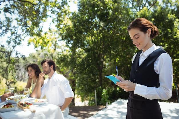 Orden de escritura de camarero sonriente en el bloc de notas