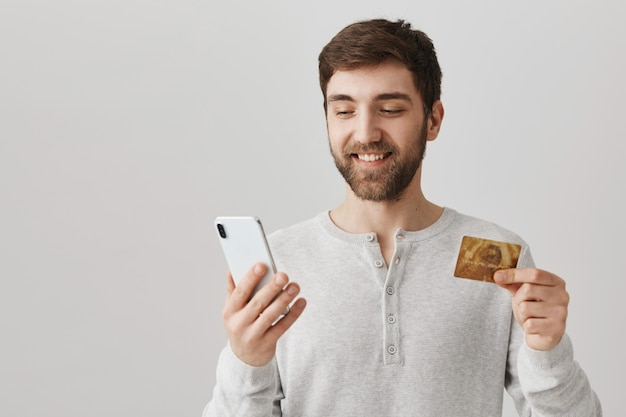 Orden de joven en línea con tarjeta de crédito, mediante teléfono móvil