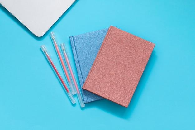 Ordenador y cartera con pincils sobre fondo azul.
