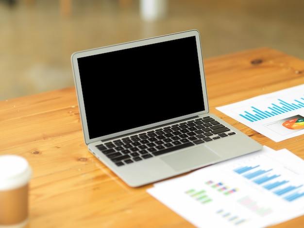 Ordenador portátil abierto en maqueta de pantalla negra con papelería de informe financiero en mesa de trabajo de madera