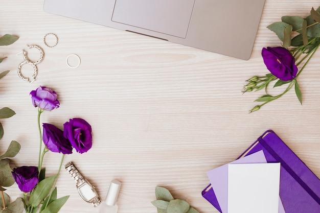 Ordenador portátil; aretes; anillos de boda; reloj de pulsera; esmalte de uñas; sobre; flores eustoma y diario sobre fondo de madera.